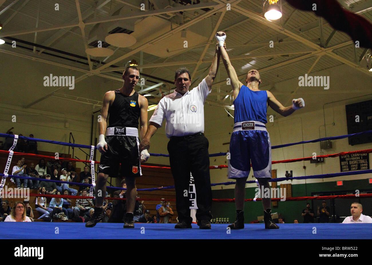 Árbitro de boxeo sostiene boxeador del brazo en el anillo después de un combate de boxeo Imagen De Stock