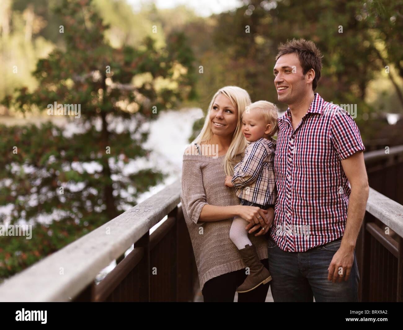 Feliz sonriente joven padres y una niña de dos años, disfrutando de la naturaleza vista desde un puente. Imagen De Stock