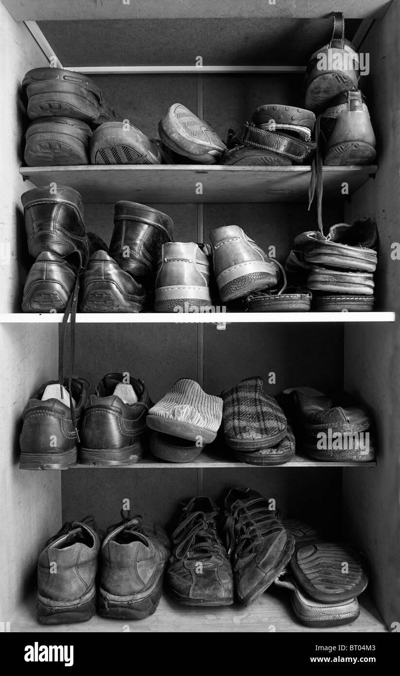 Una vieja caja de zapatos de madera con un montón de tipos diferentes de calzado en el interior. Foto de stock
