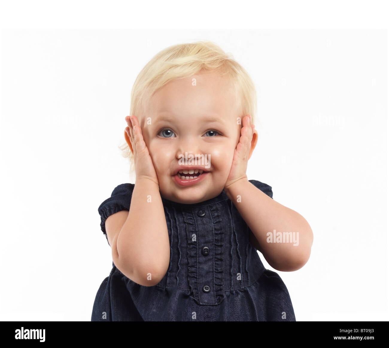 Retrato de una niña de dos años de poner una cara graciosa aislado sobre fondo blanco. Imagen De Stock