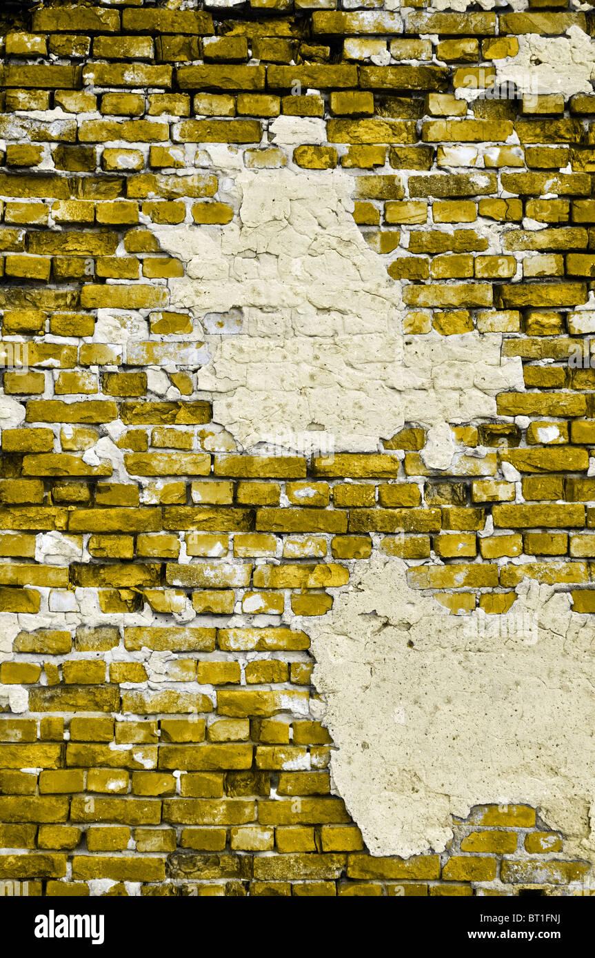 Vieja pared amarilla con grietas y manchas grises de yeso en formato vertical Imagen De Stock