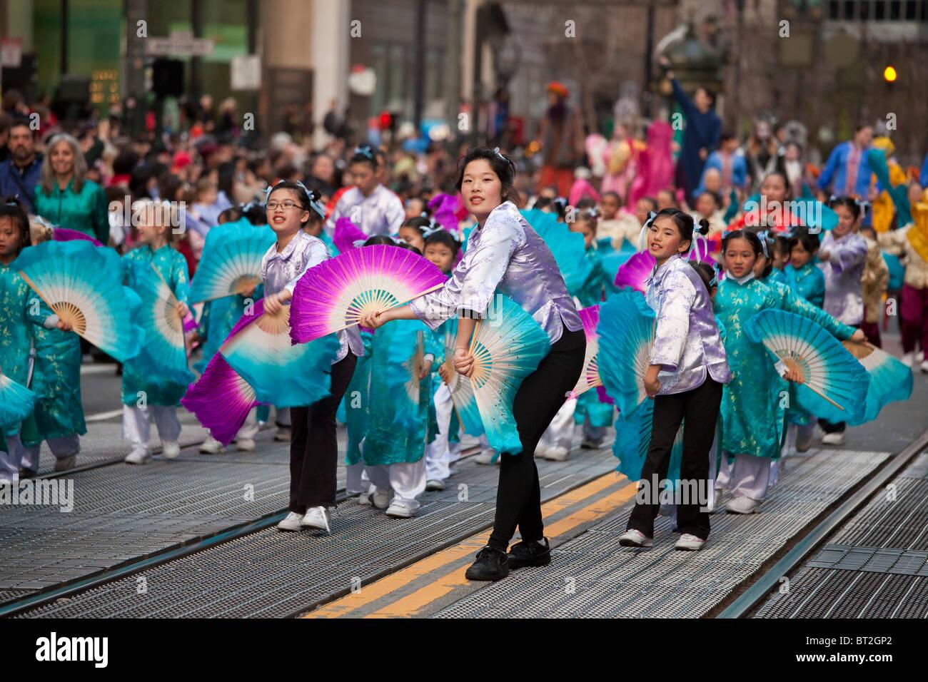Mujer China liderando un grupo de niños en el rendimiento del ventilador durante el desfile del Año Nuevo Imagen De Stock