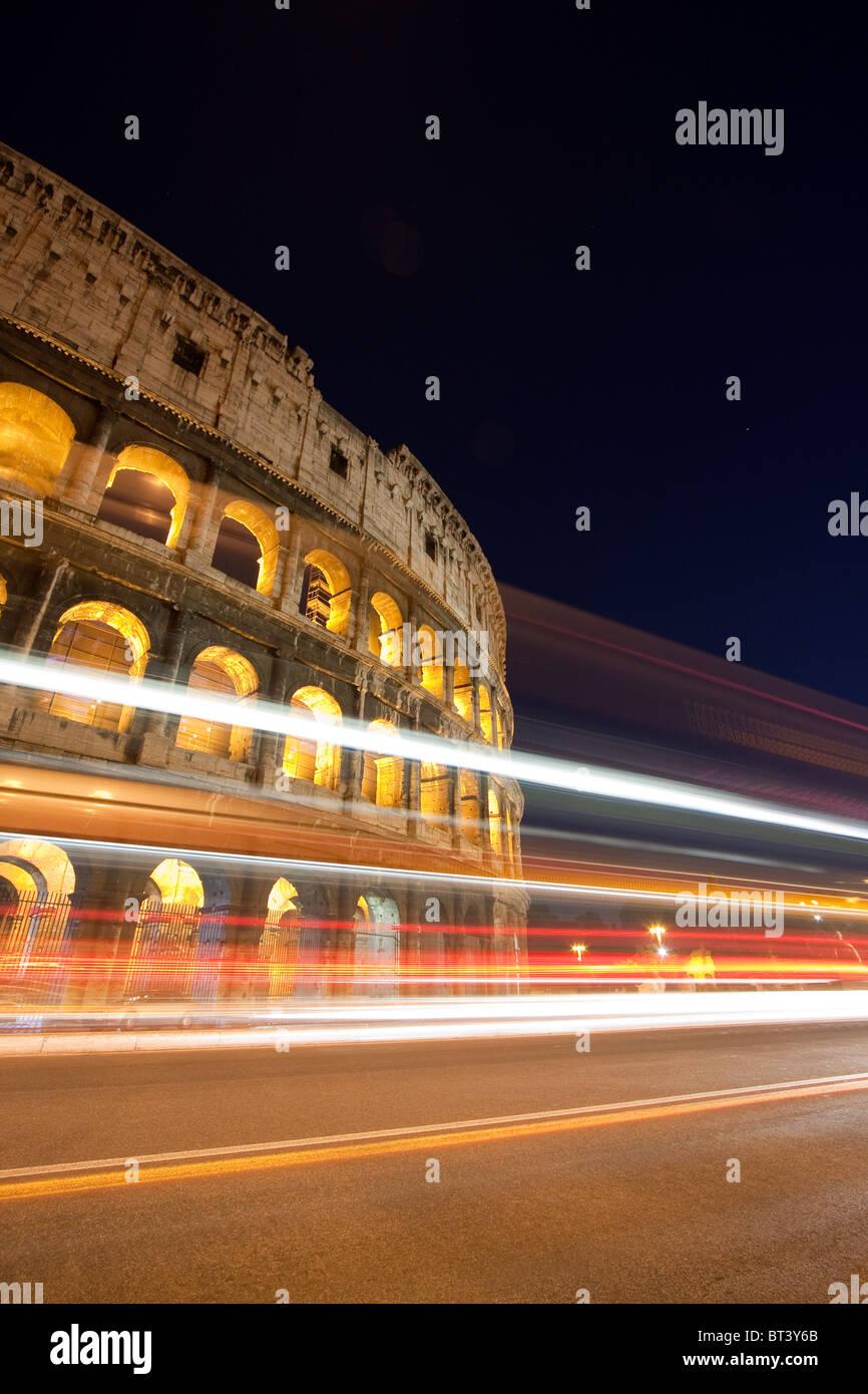 Vista nocturna del coliseo con cierto tráfico estelas de luz. Roma, Italia Imagen De Stock