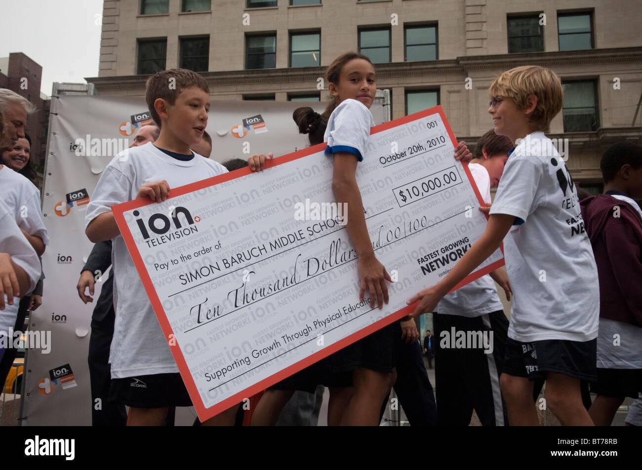 Los estudiantes de escuela intermedia reciben donación para verificar gigante programa de entrenamiento físico Imagen De Stock