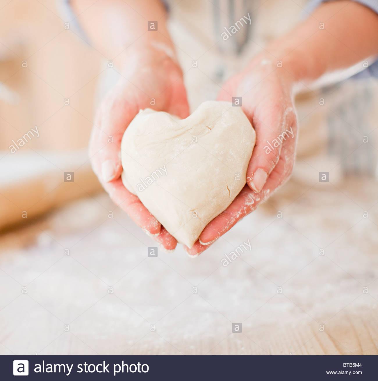 Cerca de la mujer sosteniendo la masa con forma de corazón Imagen De Stock