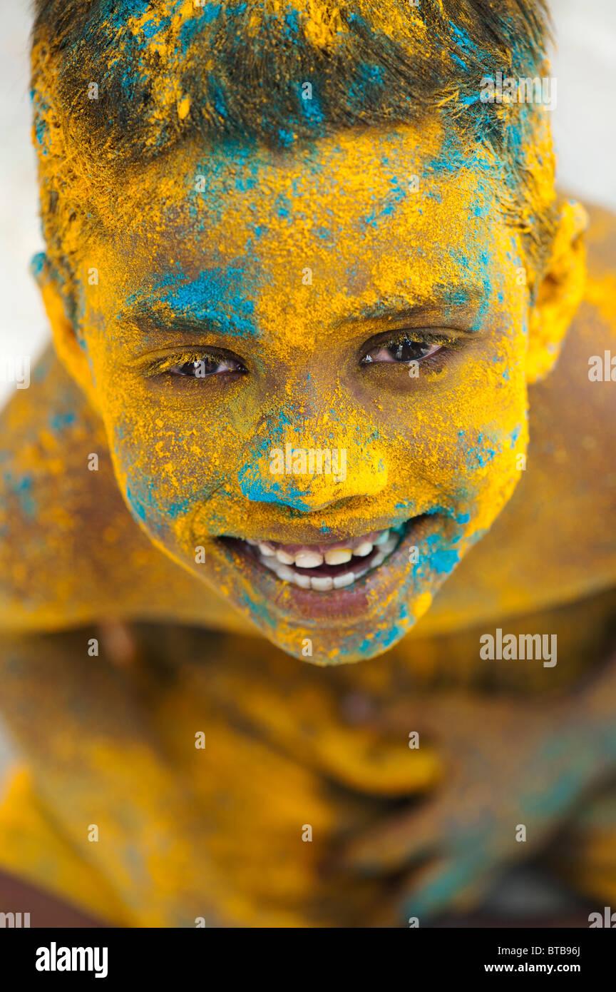 Feliz joven niño indio cubierto de polvo coloreado. La India Imagen De Stock
