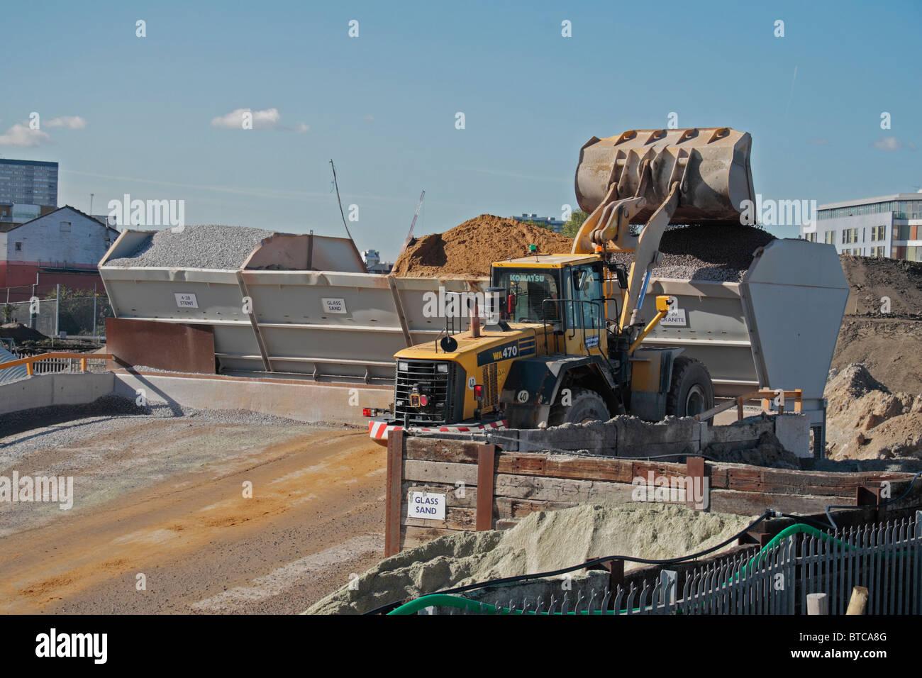 Digger depositar agregado en una de varias tolvas de producción de hormigón in situ, sitio de Juegos Olímpicos Imagen De Stock