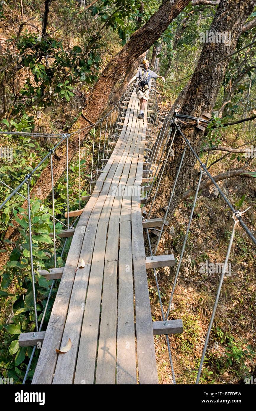 Hombre cruza uno de los puentes del cielo en una tirolesa de aventura en la zona de Chiang Mai de Tailandia. Imagen De Stock