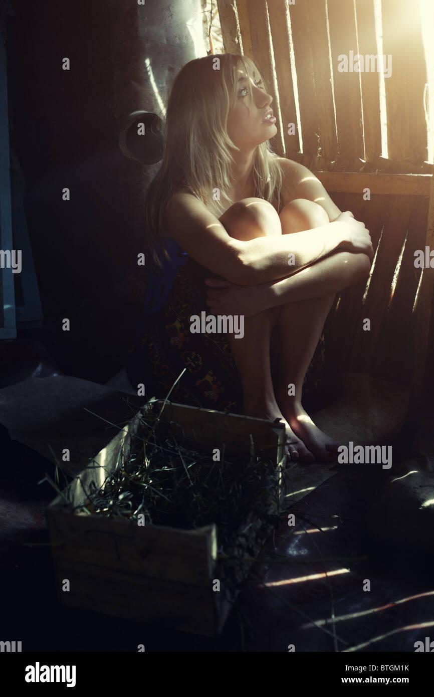 Mujer sentada en la oscuridad granero rural bajo la luz del sol. La oscuridad natural y colores Imagen De Stock