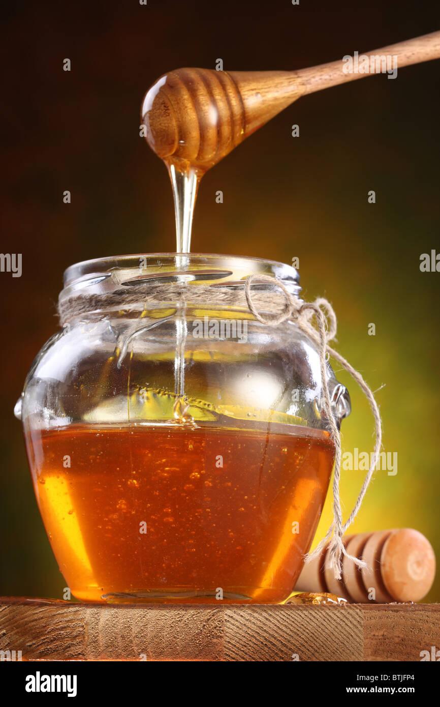 Verter la miel dulce de drizzler en la olla. Pot es sobre la mesa de madera. Foto de stock