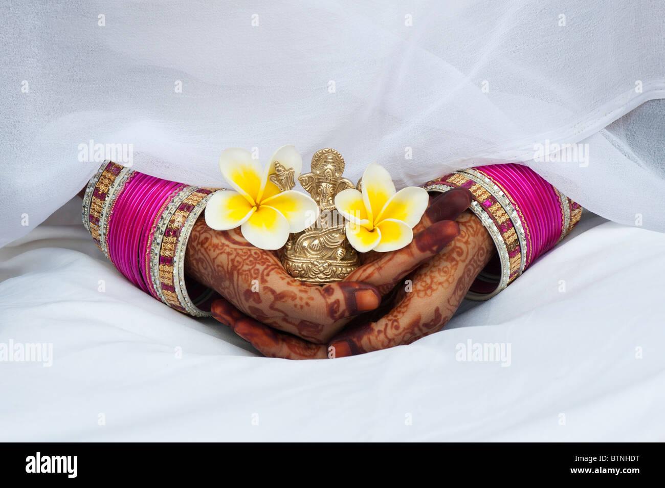 Vestida de India sari de seda blanco con henna manos sosteniendo una flor de Frangipani y una estatua de Ganesha. Imagen De Stock