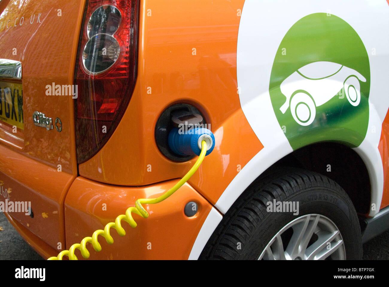 Mujer de enchufar un coche eléctrico alquilados a GoGo automóviles eléctricos EV gratis punto de Imagen De Stock