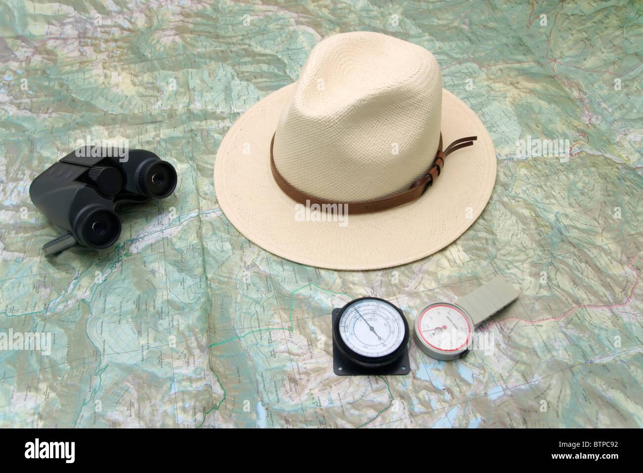 Planeando un viaje a la montaña con mapa, podómetro, altímetro, binoculares y sombrero Imagen De Stock