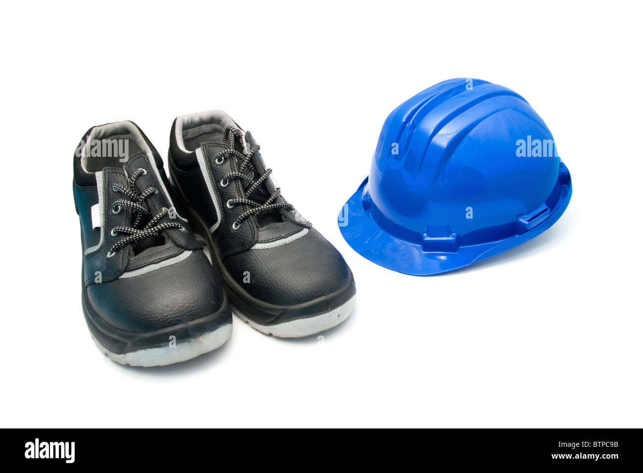Zapatos de seguridad aislado y casco azul para los trabajadores Foto de stock