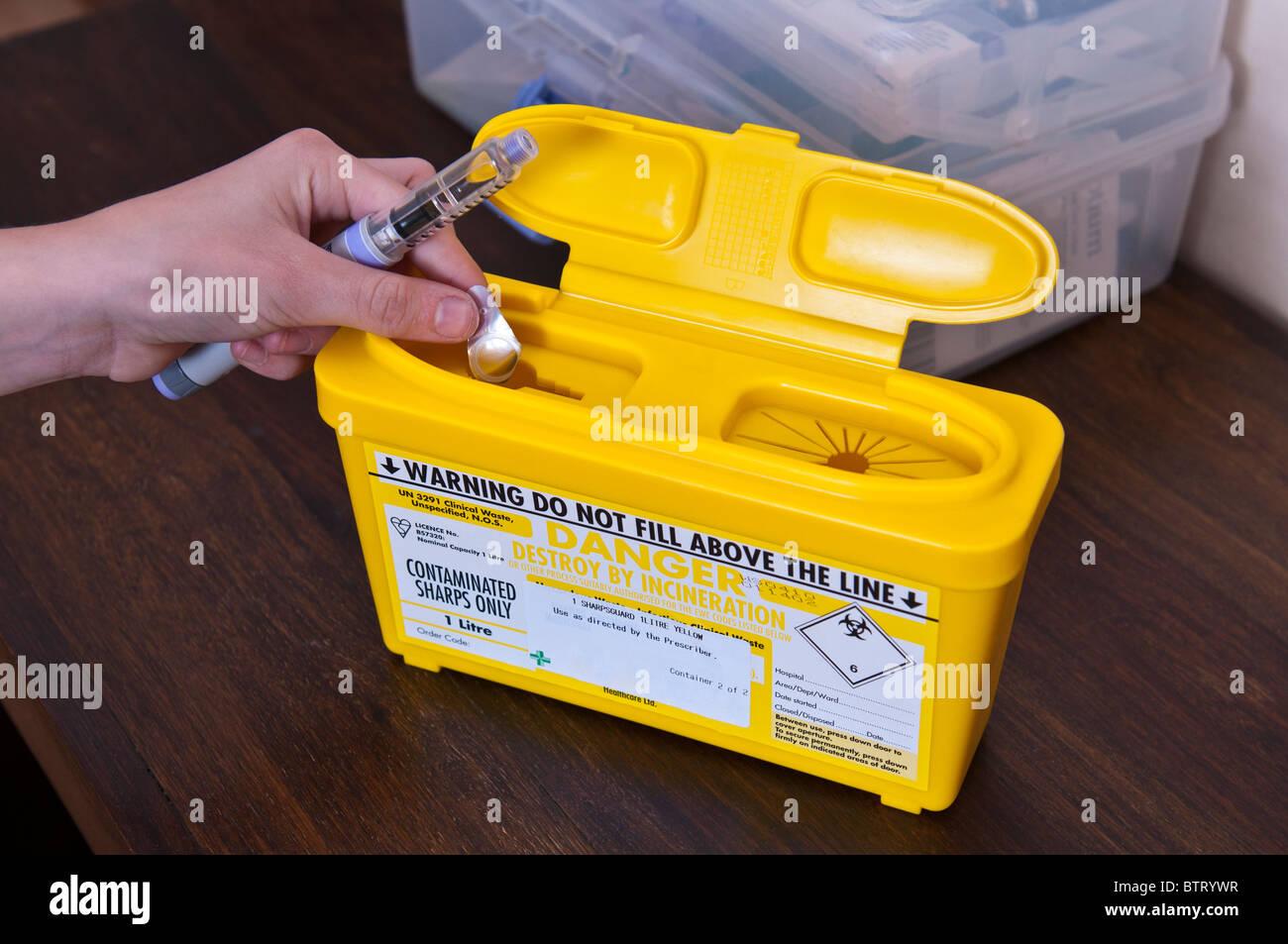 Un diabético coloca una aguja usada en un moyuelos bin después de inyectar la insulina Foto de stock