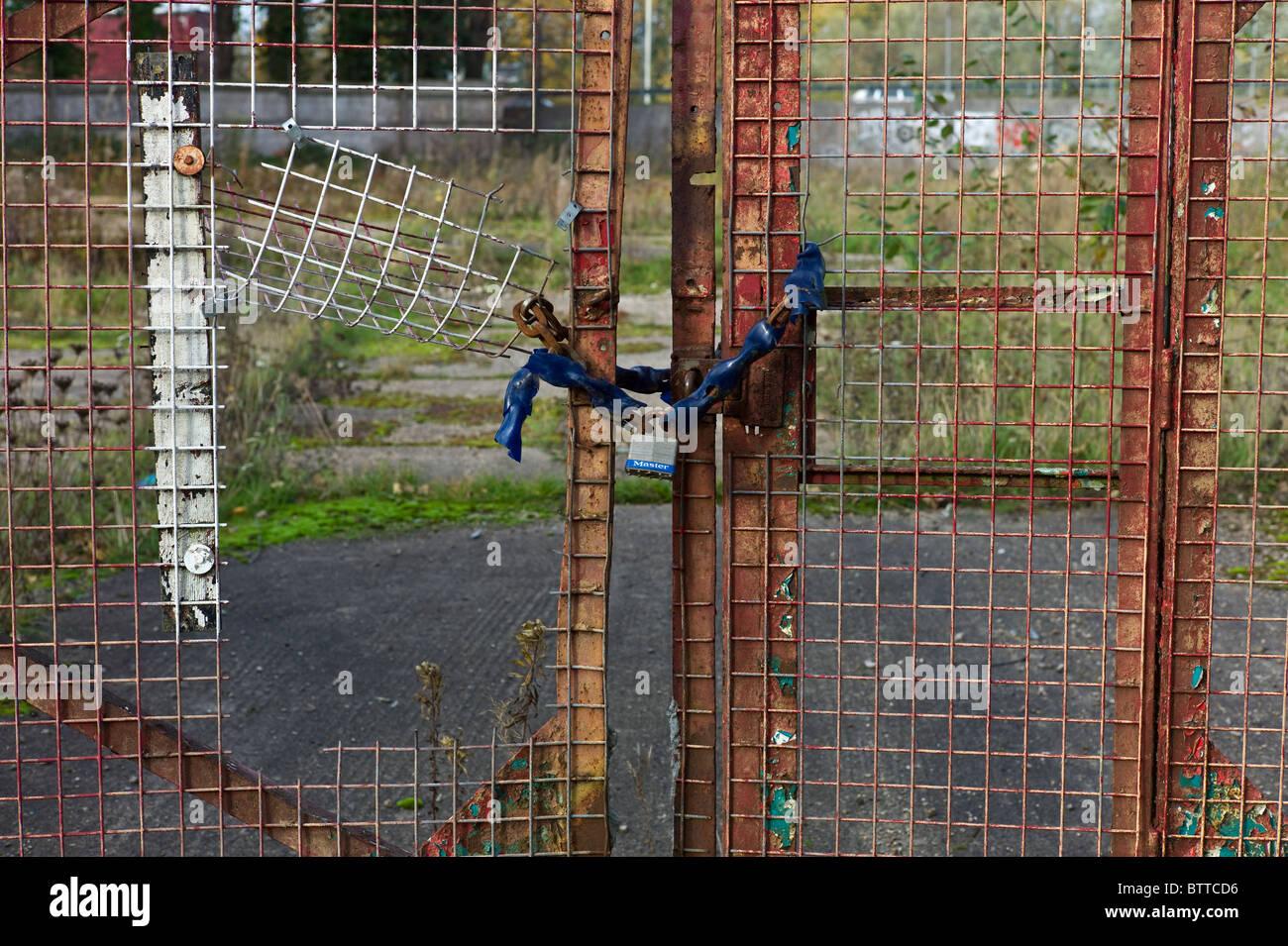 Encadenados una puerta de entrada a la wasteland sitio de una empresa en quiebra en la recesión Foto de stock