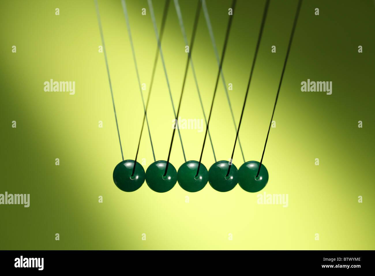 Cinco verdes canicas en fila colgando de la cadena. Ilustra Newton's cradle, un dispositivo que demuestra la Imagen De Stock