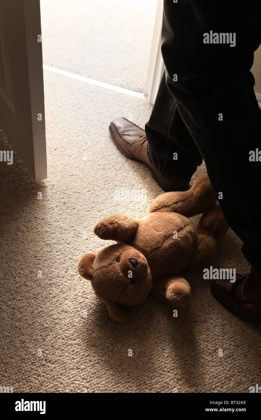 Las piernas del hombre y feett stepping pasado un oso de peluche del niño en el suelo para abandonar la habitación. Imagen De Stock