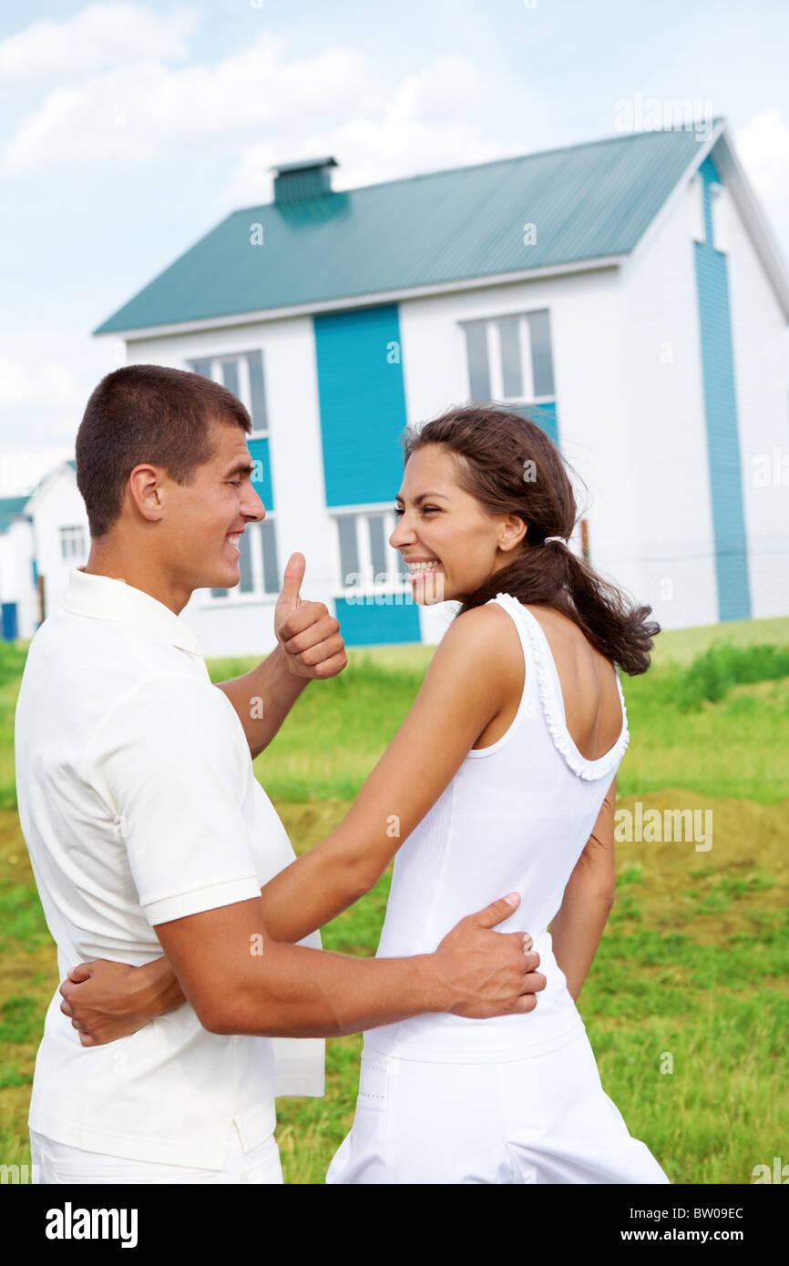 Feliz pareja sonriendo el uno al otro mientras que Guy mostrando pulgar arriba con bonita casa al aire libre Imagen De Stock