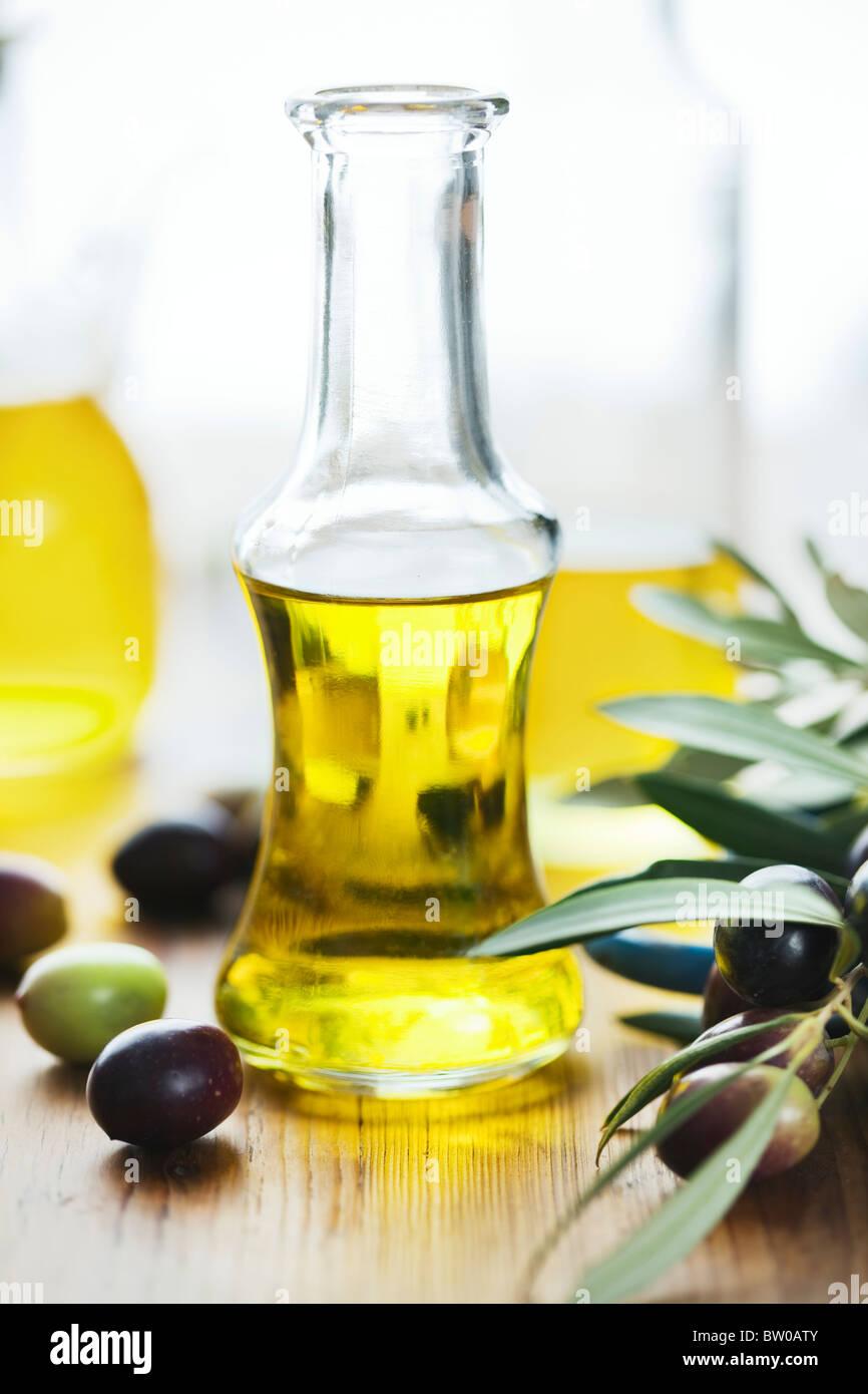 El aceite de oliva en la mesa de madera Imagen De Stock
