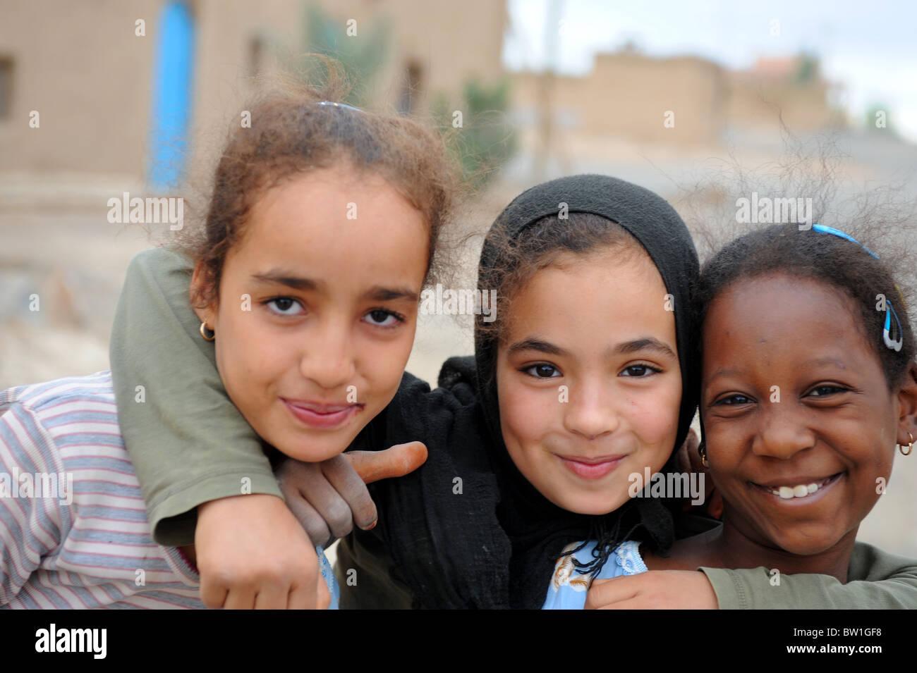 Tres niñas 9-10 años sonriendo ante la cámara. Khemliya Village, en el sur de Marruecos. Imagen De Stock