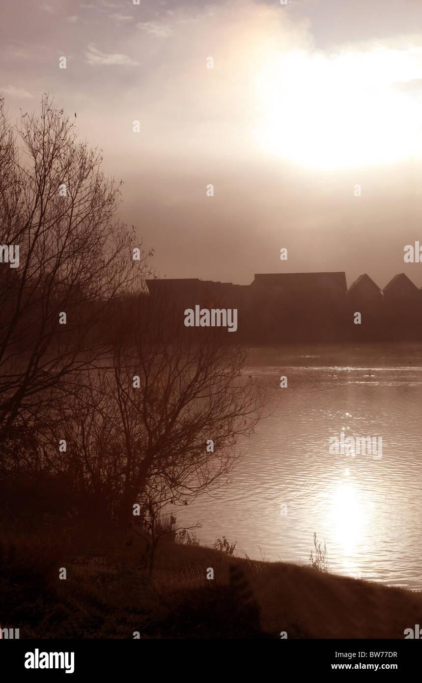 Esquema de casas en la distancia junto a un lago brumoso Imagen De Stock