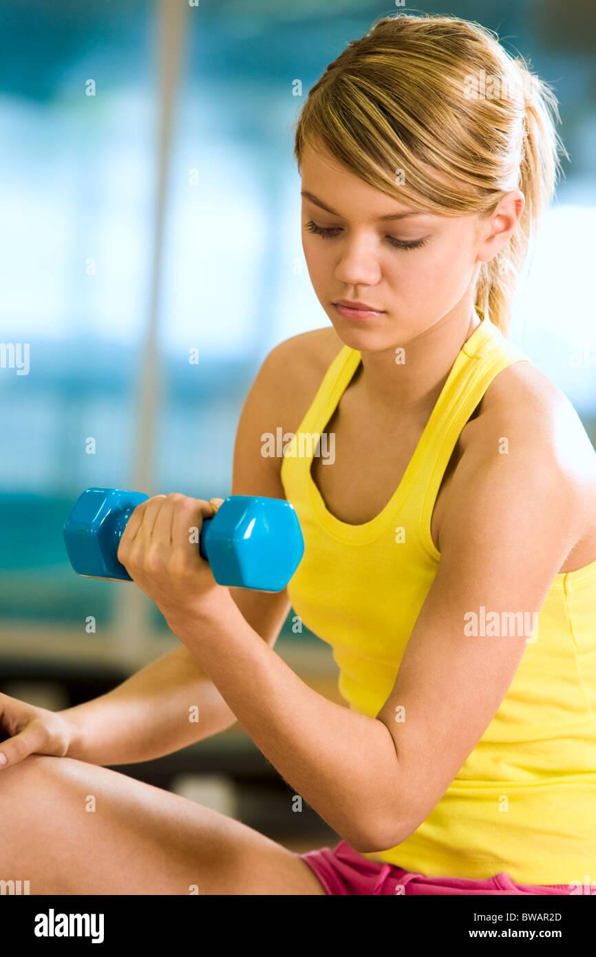 Retrato de mujer joven con pesas haciendo ejercicios para brazos fuertes Imagen De Stock