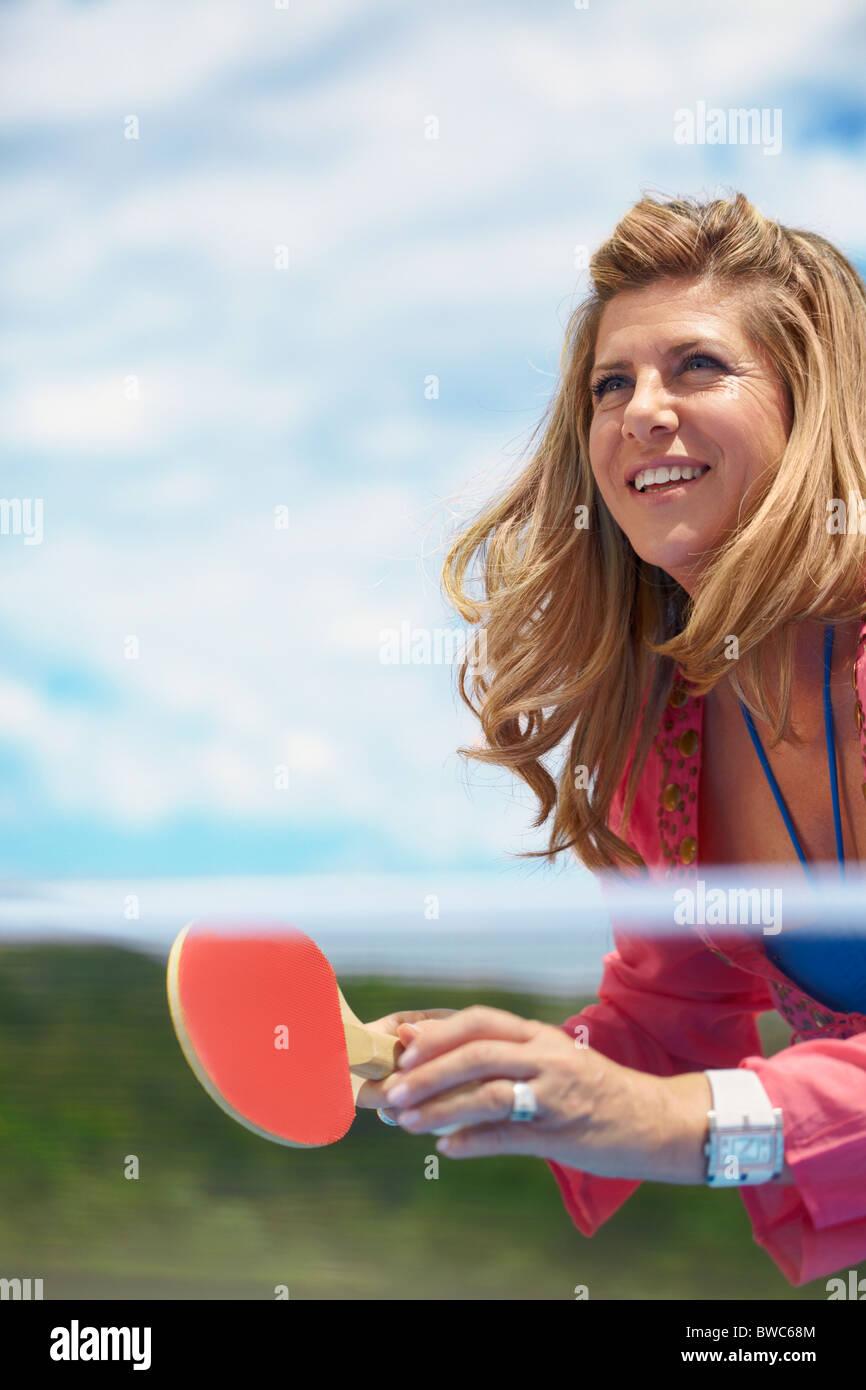 Sonriente mujer de edad jugando al tenis de mesa Imagen De Stock
