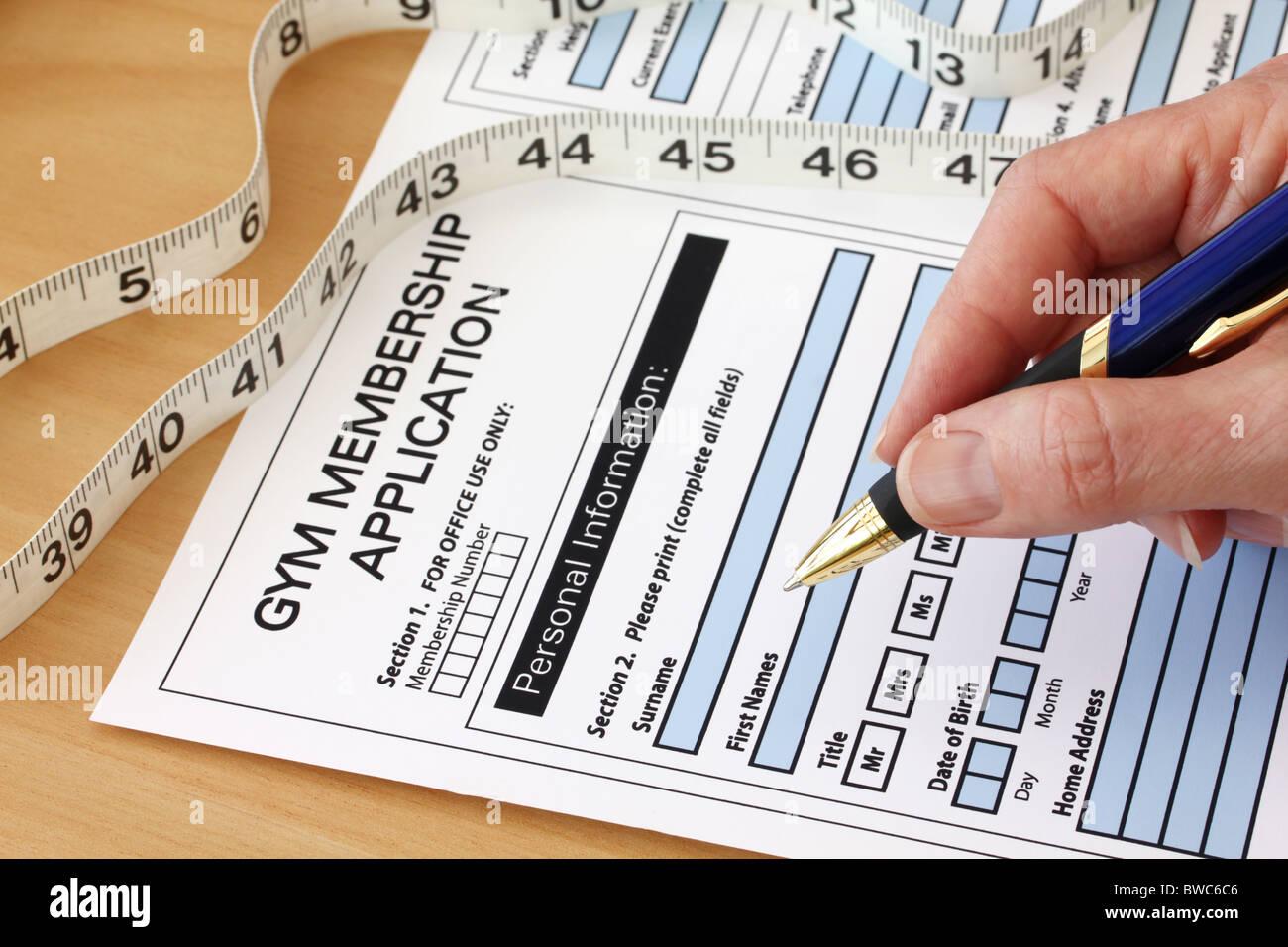 Mano con pluma gimnasio completando un formulario de solicitud de membresía Imagen De Stock