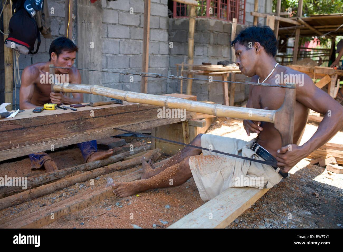 Obreros filipinos equipo vio un grueso trozo de madera narra en tablones en Mansalay, Mindoro Oriental, Filipinas. Foto de stock