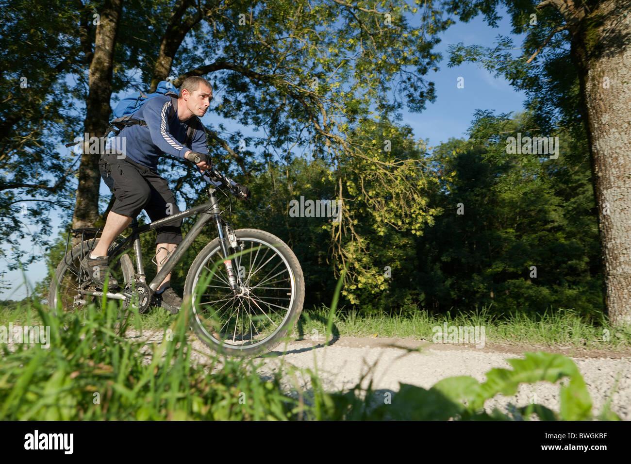 Hombre en bicicleta a lo largo de un camino de gravilla Foto de stock