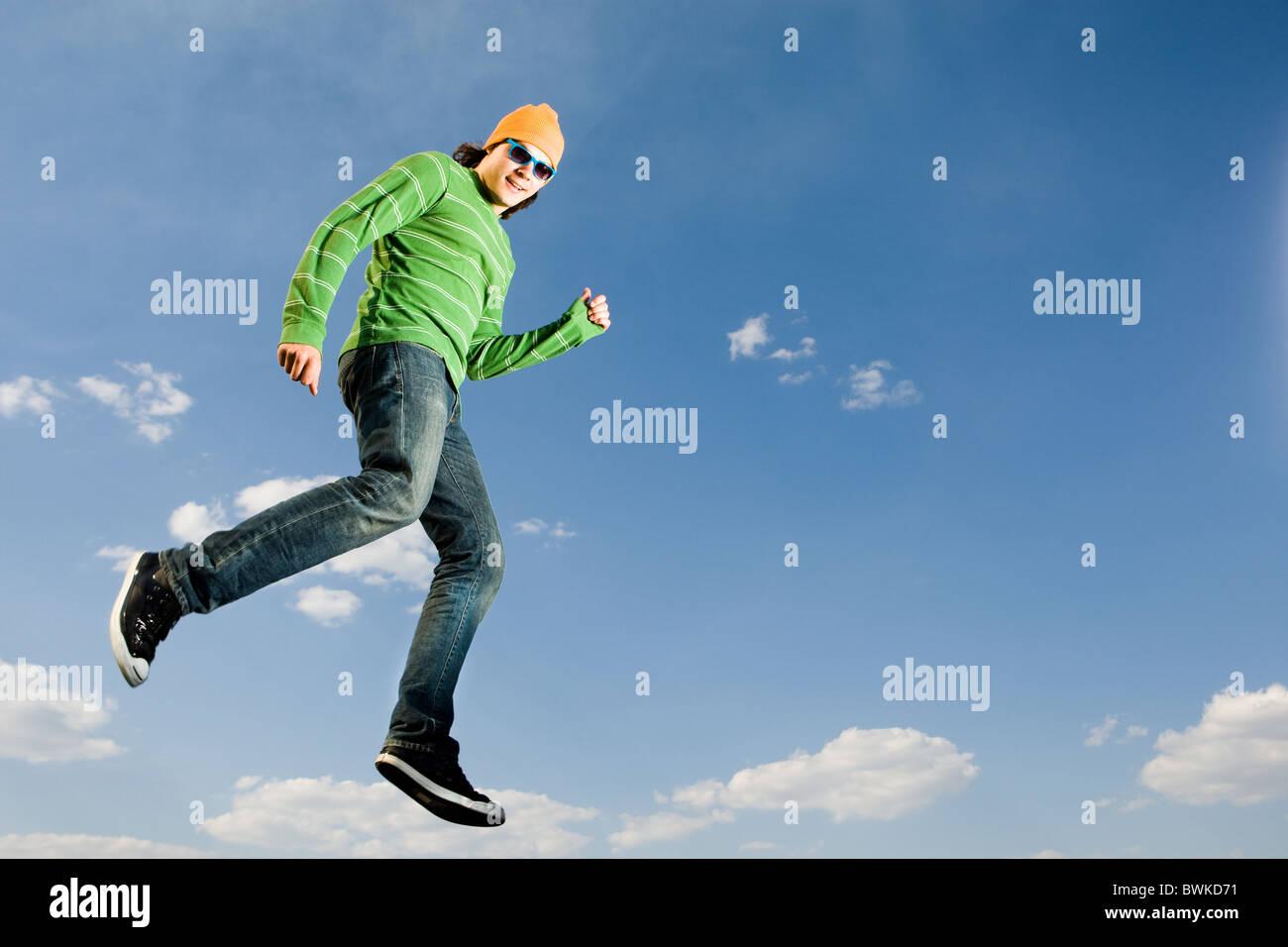 Imagen de hombre alegre en el salto de altura contra el brillante cielo azul Imagen De Stock