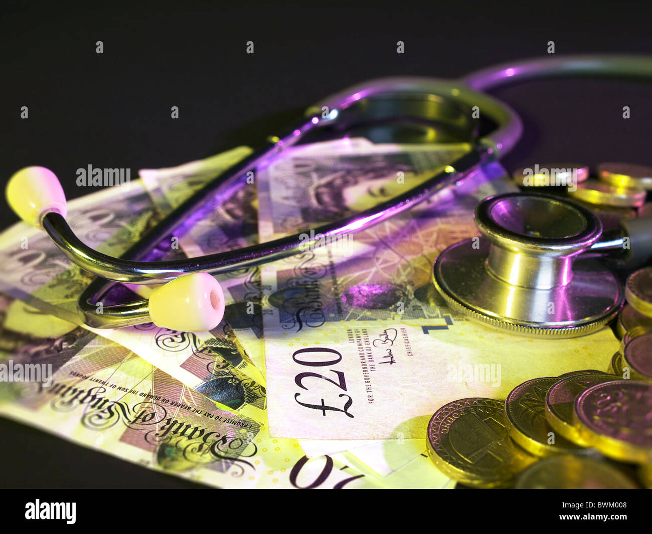 British Pound monedas apiladas en el fondo sobre un lecho de 20 libras con un estetoscopio notas Foto de stock