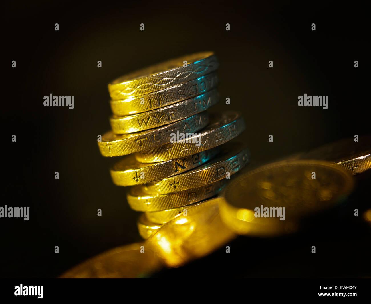 Una pila de British Pound monedas con iluminación suave se levantó entre otras monedas libra Foto de stock