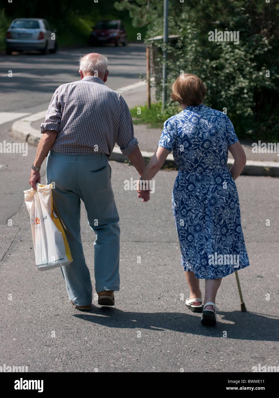 Una Pareja De Ancianos Caminando Por La Calle Tomados De La Mano En