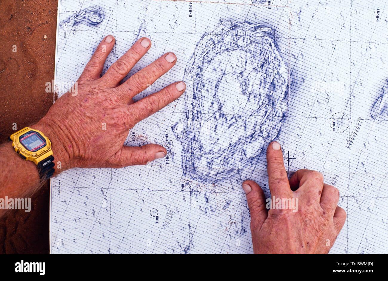 Geólogo estudiando magnético mapa de contorno, la exploración de minerales, Australia Occidental Imagen De Stock