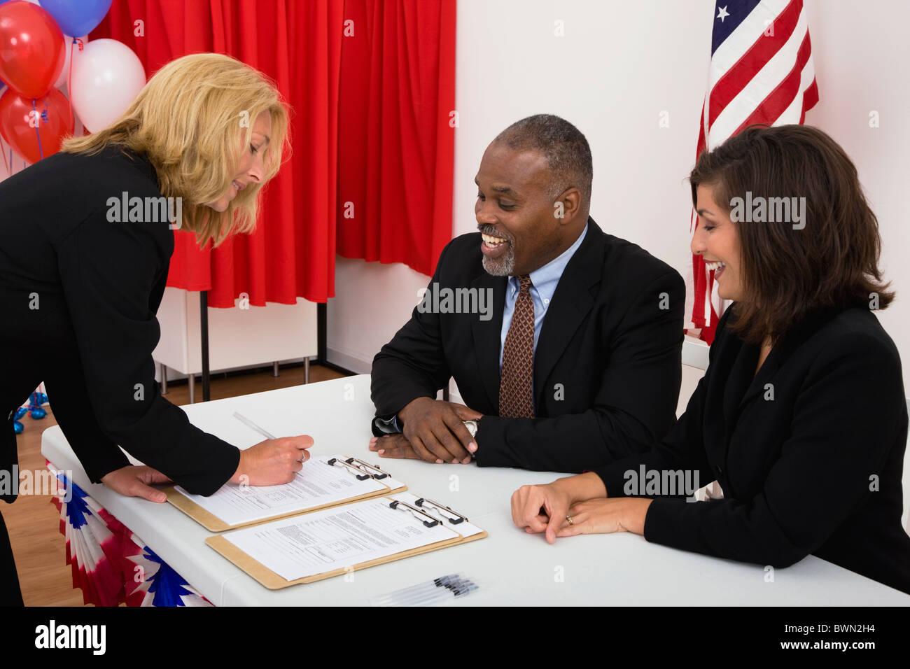 Estados Unidos, Illinois, Metamora, gente en el lugar de votación tabla, bandera estadounidense, globos y cabina Imagen De Stock