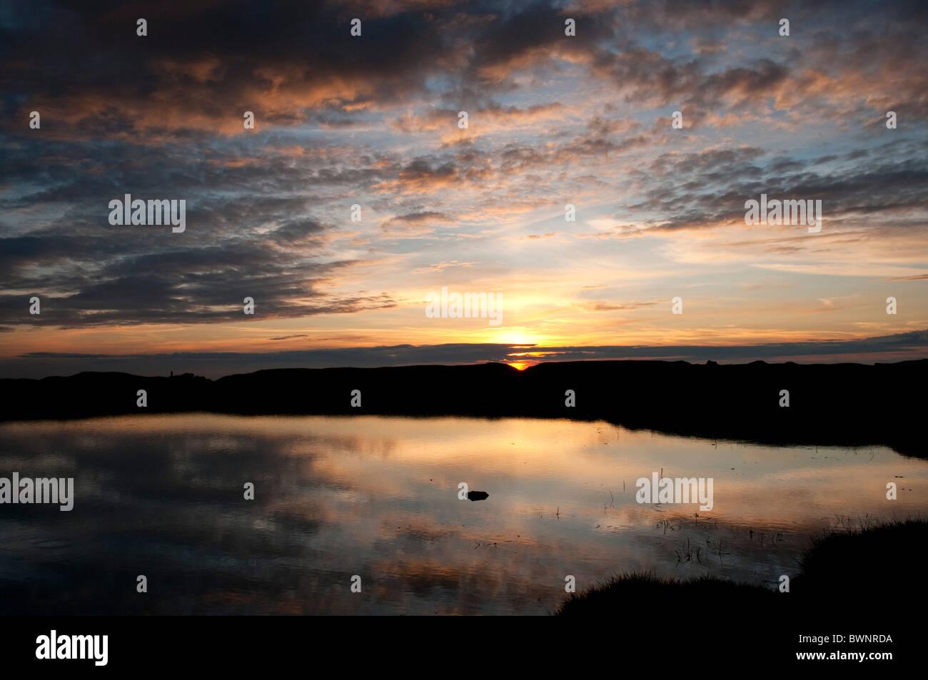 Reflexiones de la puesta de sol y nubes en el agua del estanque en Dartmoor Devon, Reino Unido Foto de stock