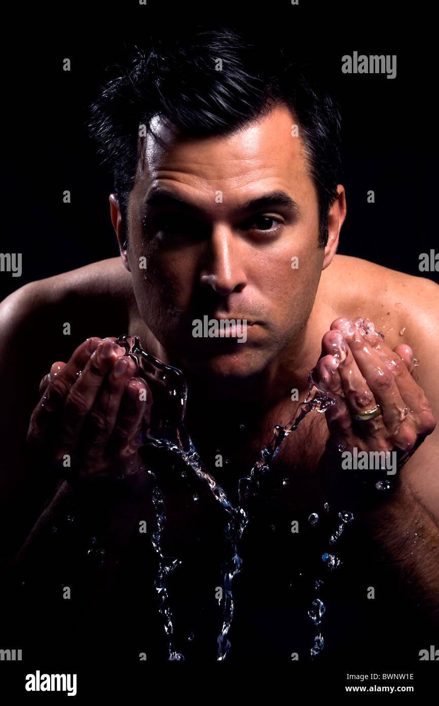 Hermoso macho lavarse la cara para despertarse por la mañana Imagen De Stock