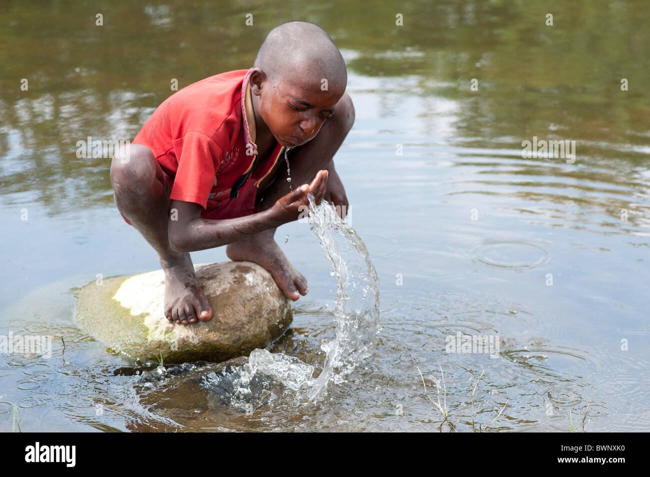 Niño de la calle indio lavarse a sí mismo y a beber agua en un río en la India rural. En Andhra Pradesh, Imagen De Stock