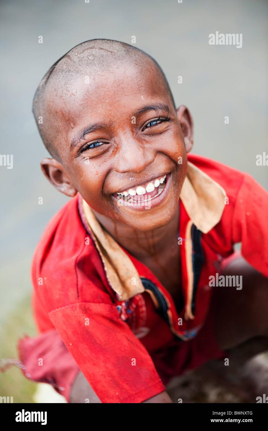 Niño de la calle indio sonriente lavarse a sí mismo en un río en la India rural. En Andhra Pradesh, India Foto de stock