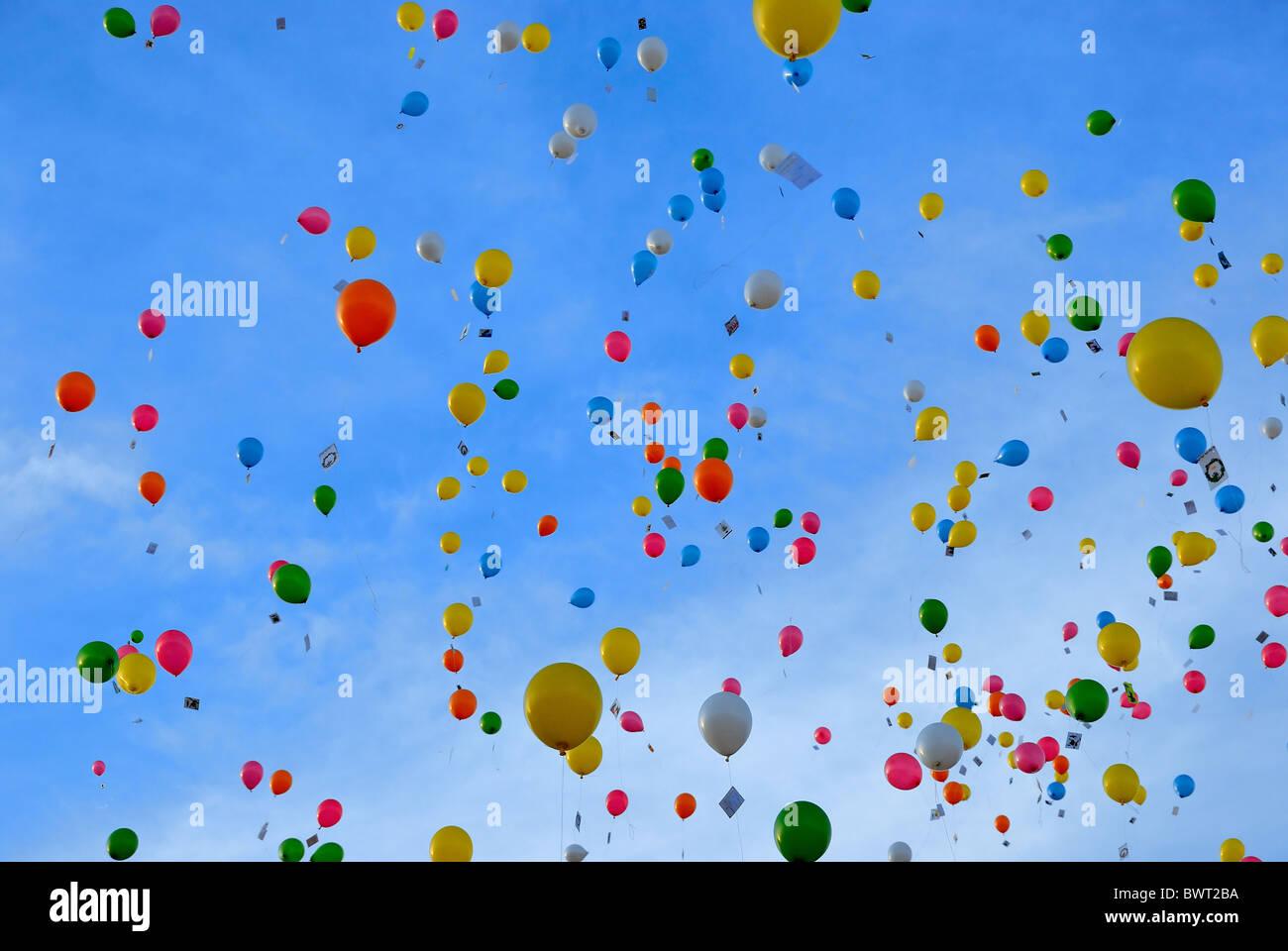 Globos de colores brillantes que flotan en un cielo azul. Imagen De Stock
