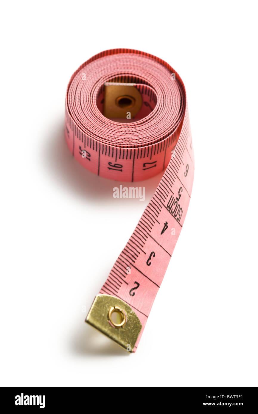Cinta métrica de color rosa sobre fondo blanco. Imagen De Stock
