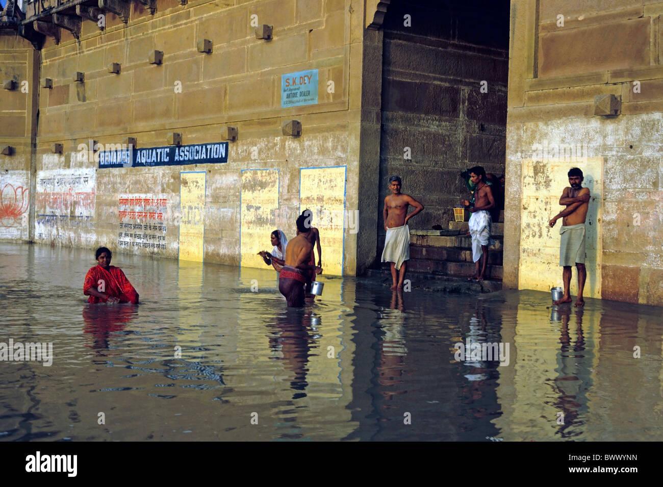 Los hombres y mujeres que realizan las abluciones en el río Ganges, Varanasi, India. Imagen De Stock