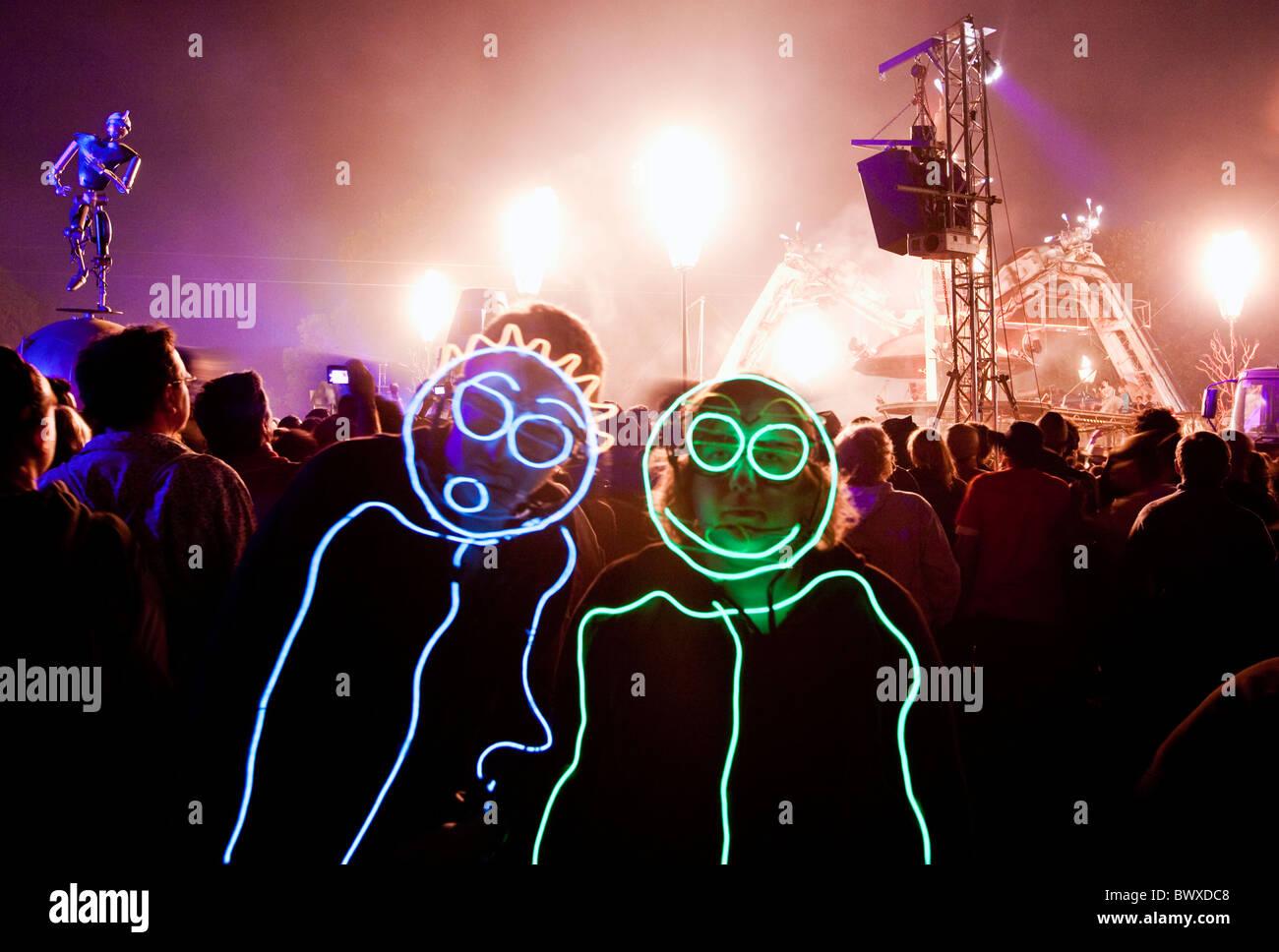 Los asistentes al festival en trajes luminosa cerca de Arcadia festival Glastonbury Somerset, Reino Unido Europa Imagen De Stock