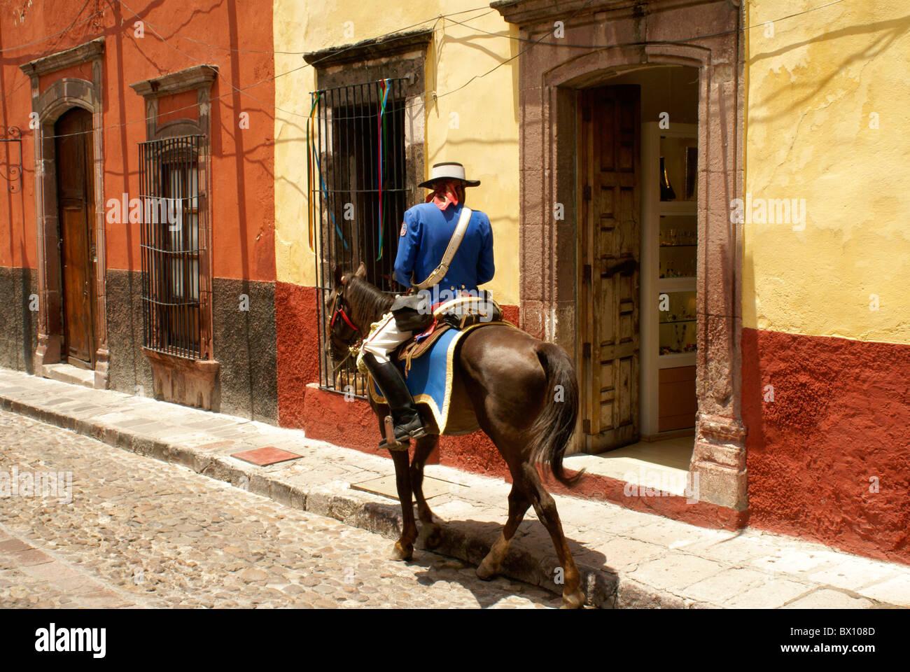 Un policía español en traje tradicional patrullando una calle en San Miguel de Allende a caballo , México. Imagen De Stock