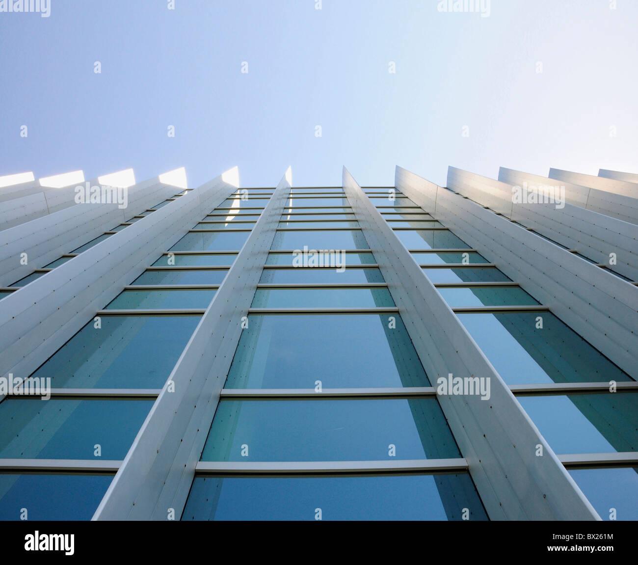 Ventanas exteriores de un edificio de oficinas comerciales, mirando hacia arriba desde el suelo con el cielo azul Imagen De Stock