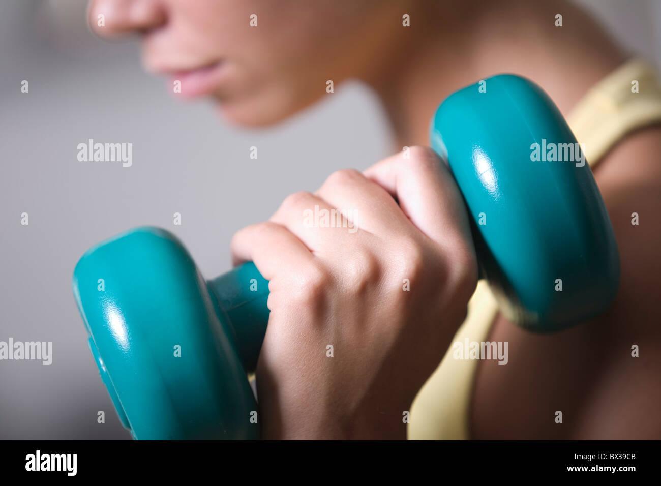 Close-up de joven ejerciendo con dumb bell Imagen De Stock