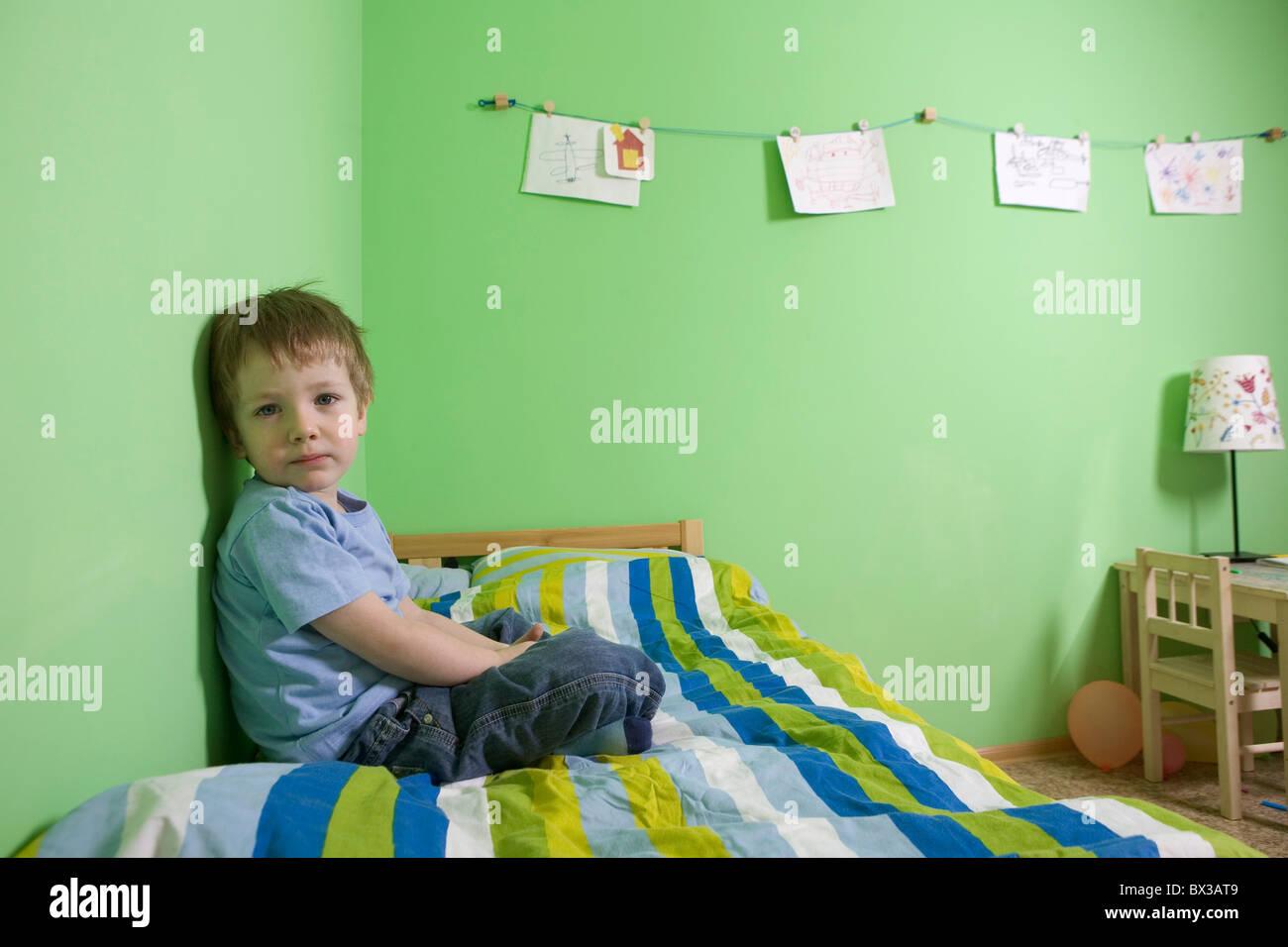 Joven sentada en la cama en la habitación de los niños Imagen De Stock