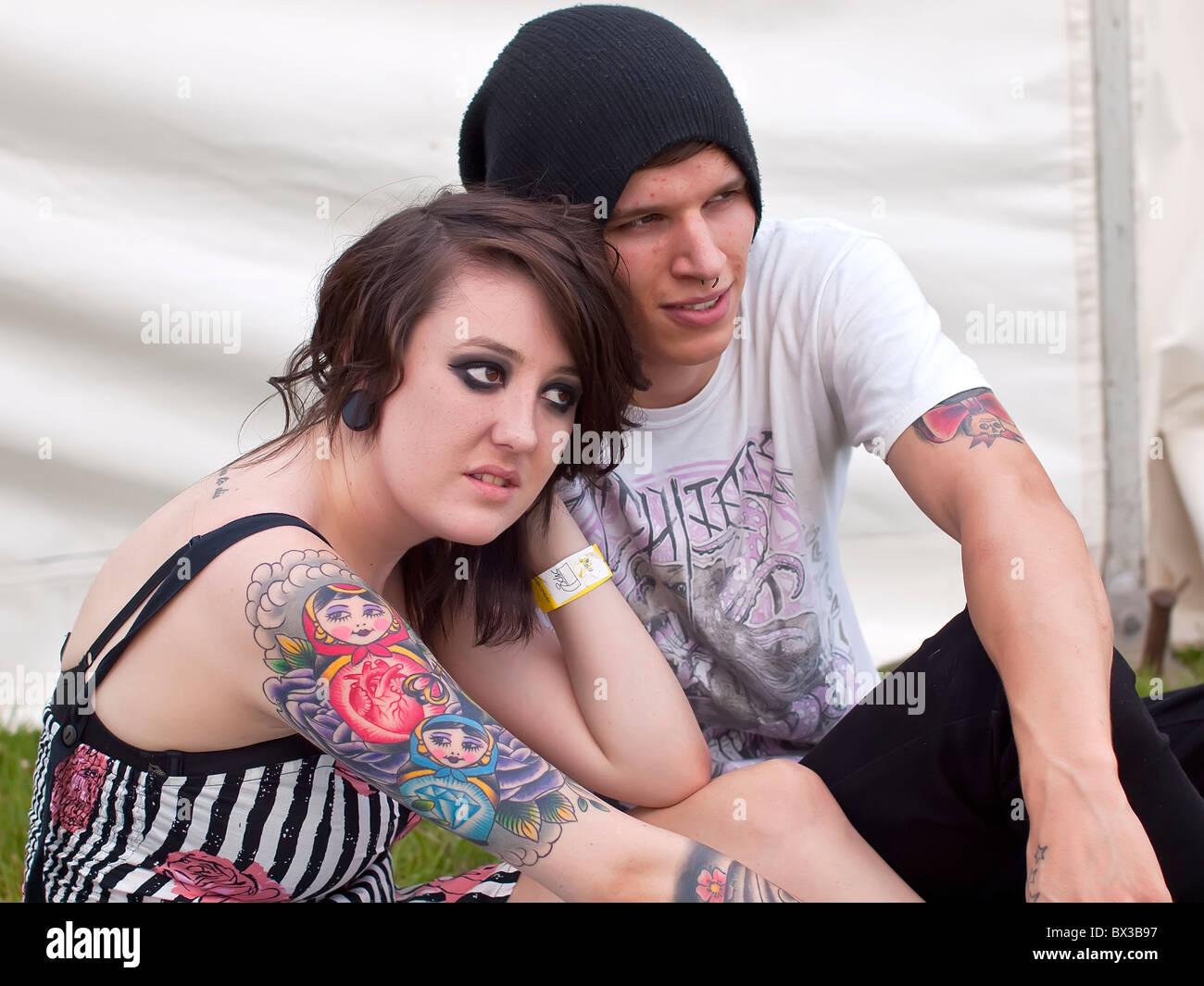Lucy una moda joven mujer adulta de 19 años con tatuajes con muchacho amigo Blair (personas reales) en el festival Foto de stock